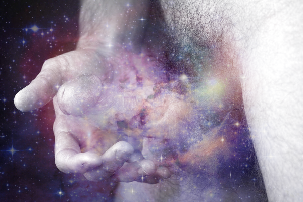 A man's hand beholds his penis which is shrouded in an aura of stars, light and colour.